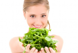 picture of happy woman with spinach over white