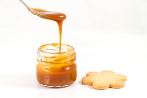 Pouring caramel in a small jar with spoon, horizontal