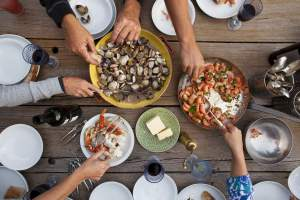 Hands serving shellfish meal around wooden table
